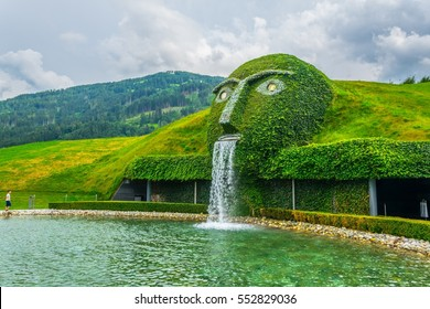 Fountain with giant head spitting water into a pond at swarovski Kristallwelten in Wattens, Austria.