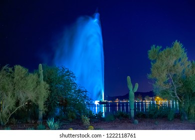 Fountain Hills, AZ has one of the tallest fountains in the world. The water shoots into the night sky surrounded by lake water, saguaro cactus, reflecting lights and trees in this nature image