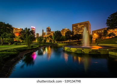 Fountain and lake at Marshall Park and the Uptown skyline at night, in Uptown Charlotte, North Carolina.