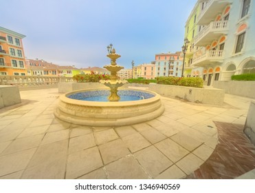 Fountain at little Venice in venetian style. Colorful houses in picturesque Qanat Quartier icon of Doha, Qatar at sunny day with blue sky. Venice at the Pearl, Persian Gulf, Middle East.