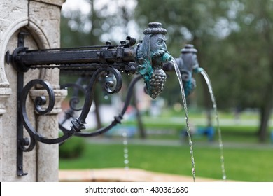 Fountain man head water tap in Valley of the Beautiful Women in Eger, Hungary