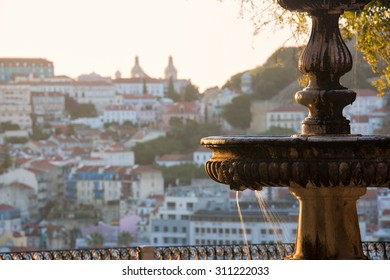 Fountain at a miradouro in Lisbon, capital of Portugal, lit by the first yellow light of the sun with church and fortress in the distance blurred by background blur leaving room for copy space