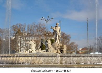 Fountain of Neptune (Fuente de Neptuno). Winter photo of the neoclassical style statue of Neptune and horses at the center of the Canovas del Castillo square in Madrid, Spain.