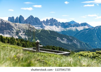 Fountain on pasture with a beautiful view on the Geisler alm from the plose (italian dolomites)