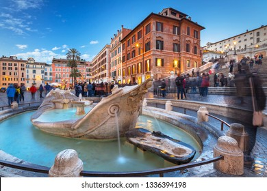 Fountain on the Piazza di Spagna square and the Spanish Steps in Rome at dusk, Italy