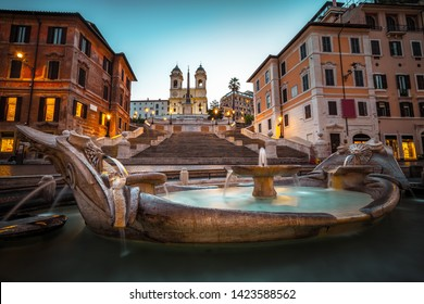 Fountain on the Piazza di Spagna square and the Spanish Steps in Rome at dusk