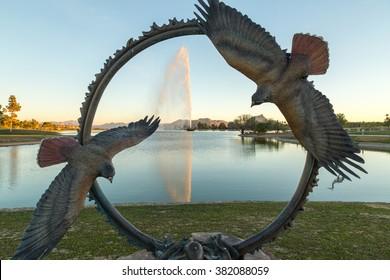 Fountain Park in Fountain Hills, Arizona.  The fountain seen through a circular bronze sculpture with hawks at sunset