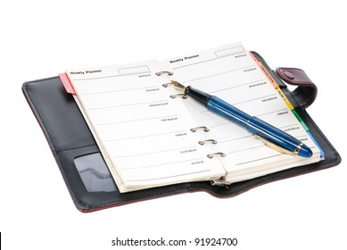 Fountain pen and diary on white background