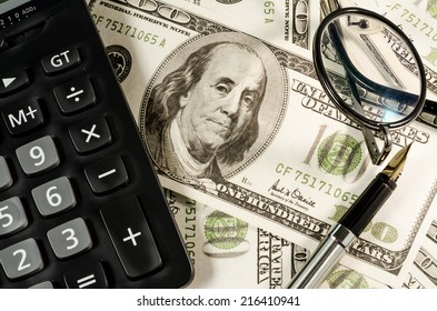 Fountain pen glasses and  calculator  on the  Hundred  Dollars