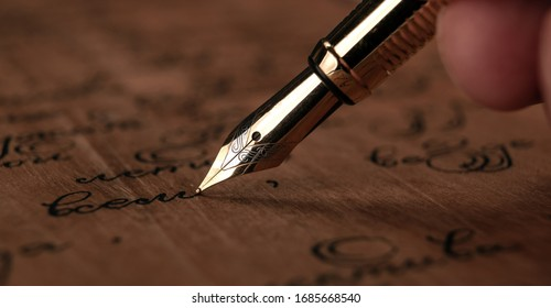 fountain pen in the hand with paper with ink text on the wooden desk closeup