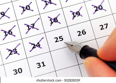 Fountain pen in human hand marking days on calendar. Focus on calendar.