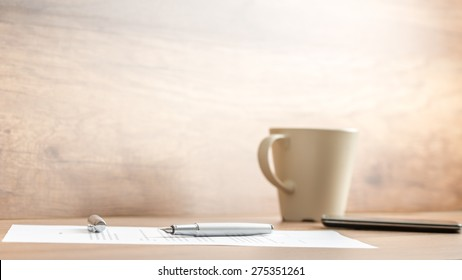 Fountain pen lying on office paperwork alongside a mug of coffee viewed low angle against a rustic or vintage style wall with copyspace.