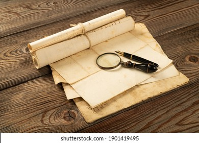 Fountain pen and magnifying glass with old sheets on wood background