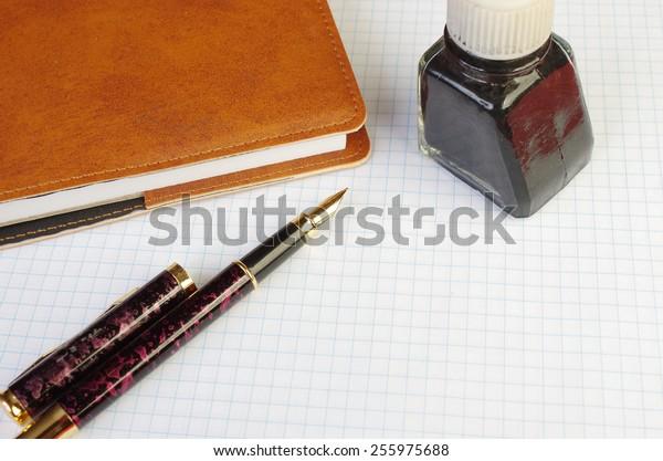 Fountain pen, notebook, inkpot