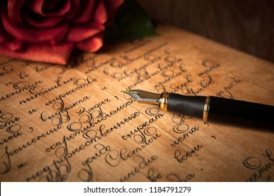 fountain pen on letter with text and red rose close up