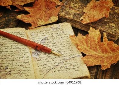 Füllfederhalter auf alten handgeschriebenen Büchern mit Herbstblättern