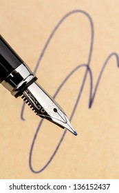 a fountain pen and a signature on yellow paper. symbolic photo for contract, and graphology testament