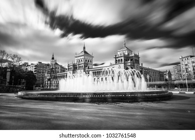 Fountain in the Plaza Zorrilla square in Valladolid, with the Cavalry Academy building in the background. Long exposure.