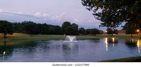 Fountain in a pond with tree lime and clouds with light reflection on water