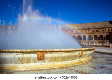 Fountain and rainbow on square of Spain in Seville, Spain