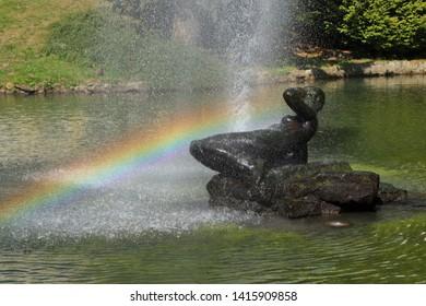 Fountain with sculpture of woman lying on rock. Rainbow in water drops. Famous spa. Marianske Lazne (Marienbad), Czech Republic.