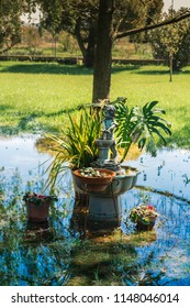 Fountain with small statue on grass field waterlogged