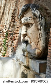 Fountain with spout in the shape of a human face with large sink