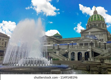 Fountain spraying water in front of the stairs at the Soldiers Grove entrance to the domed Capital building that is the State seat of government in Harrisburg.