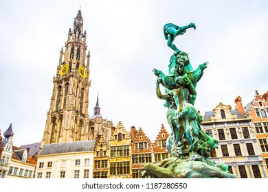 Fountain statue of Brabo throwing the severed hand of Antigoon into the Scheldt river with belfry of the Cathedral of our Lady, Antwerp, Belgium