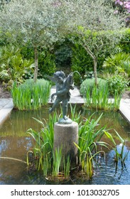 Fountain Statue in a Pond in a Country Cottage Garden in Rural Cornwall, England, UK