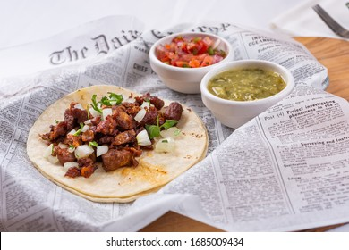 Fountain Valley, California/United States - 05/09/2019: A closeup view of an al pastor taco with condiments, in a restaurant or kitchen setting.