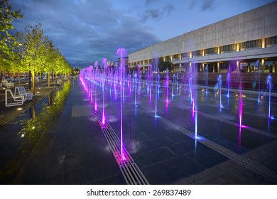 Fountains Road. Trees and dry fountain with lights on Moscow embankment at night.