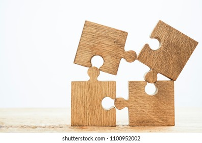 Four 4 brown pieces of puzzle stand on wooden table isolated on white background. empty copy space for inscription or objects. idea, sign, symbol, concept of connecting