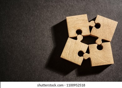 four 4 wooden puzzle, jigsaw lie on black paper background.