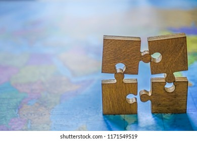 four 4 wooden puzzle on world map background. empty copy space for inscription or other objects. Concept of Globalization.