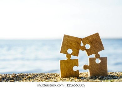 four 4 wooden puzzles standing on sand beach on on blue sea and sky background. family on resort idea.