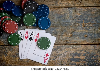 four aces with casino chips on wooden table