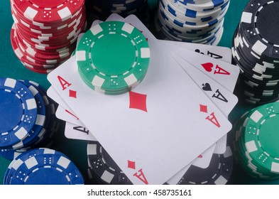 Four aces with a lot of chips on the poker table.