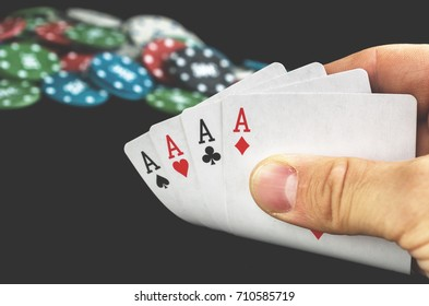 Four aces in hand with poker chips on black blurred on background. Casino win concept