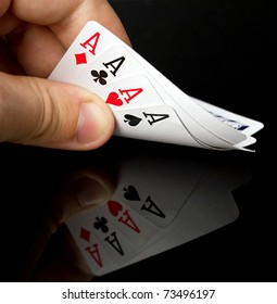 Four aces in the hand with reflection