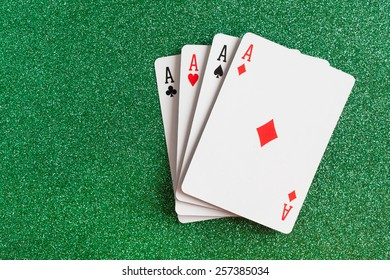 Four aces playing cards suits on green