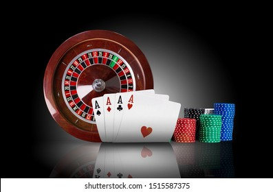 Four aces standing on mirror surface with backlight, ahead of brown roulette and chips in piles. Black background. Gambling entertainment. Close-up.