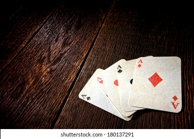 Four aces vintage poker game playing cards on a weathered wood table in an old western frontier gambling establishment saloon