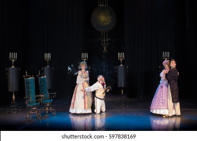 Four actors play roles on stage, a young man in an old frock coat, an elderly man in military uniform and wearing a cocked hat and two female actresses in medieval dresses with wide skirts
