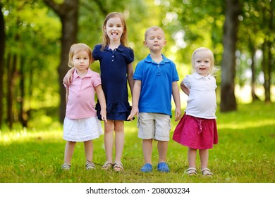 Four adorable little kids outdoors at summer day