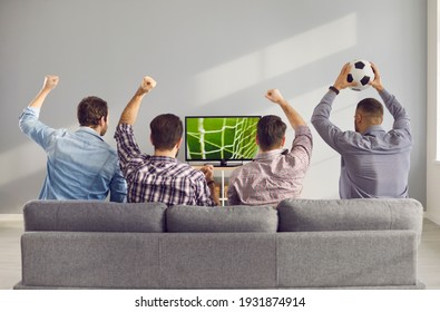 Four adult male friends with arms raised emotionally watching a football match on TV at home. Unrecognizable friends sit on the couch with their backs to the camera and cheer for their favorite team.