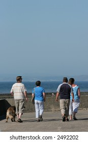Four adults out for a stroll on a beach promenade in summer, one with a dog, with the sea in the distance.