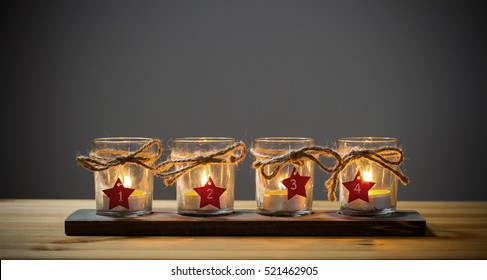 Four Advent candles on grey, fourth Advent