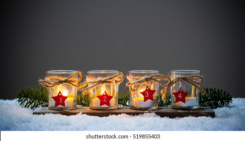 Four Advent candles in the snow, third Advent