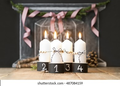 four advent christmas candles in black and white
